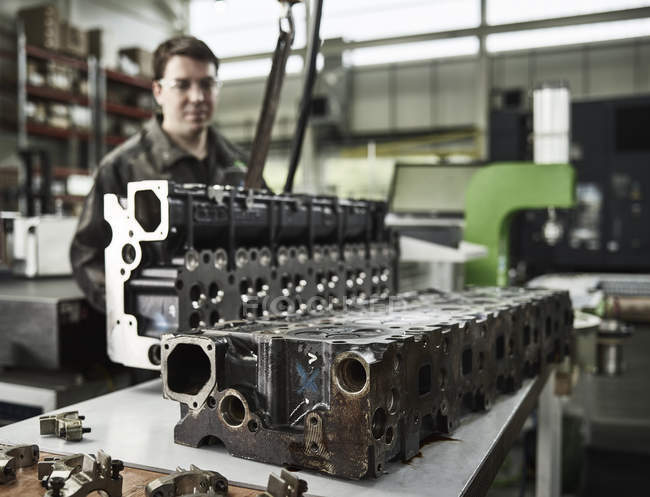Worker in metalworking factory lifting cylinder head with crane — Stock Photo