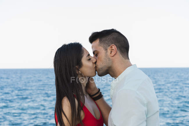 Young romantic couple kissing on background of sea - foto de stock