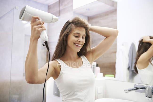 Ritratto di donna ridente con asciugacapelli in bagno — Foto stock