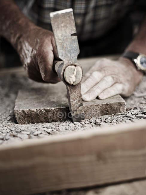 Каменщик, работающий на камне молотком — стоковое фото