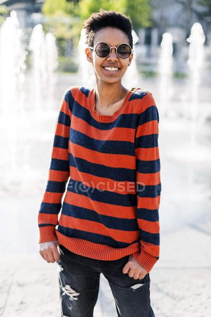 Портрет усміхнена молода жінка, що носить сонцезахисні окуляри і смугастий пуловер — стокове фото