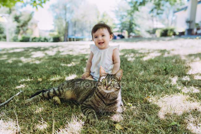 Портрет табби-кошки на лугу со смеющейся девочкой на заднем плане — стоковое фото