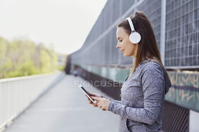 Woman with headphones using smartphone — Stock Photo