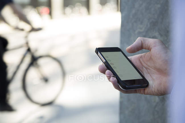 Hand of businessman holding cell phone - foto de stock
