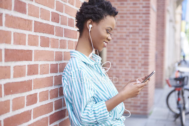 Smiling woman with earphones using cell phone — Stock Photo