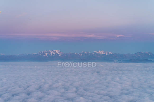 Flight above the clouds with mountains in background — Stock Photo