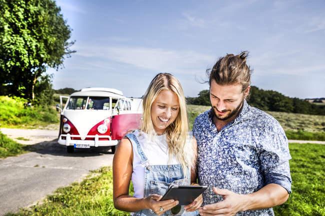 Щаслива пара за межами фургона в сільській місцевості дивиться на табличку. — стокове фото
