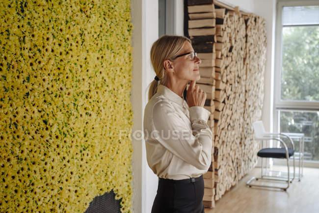 Geschäftsfrau im Büro an Wand mit Sonnenblumen — Stockfoto