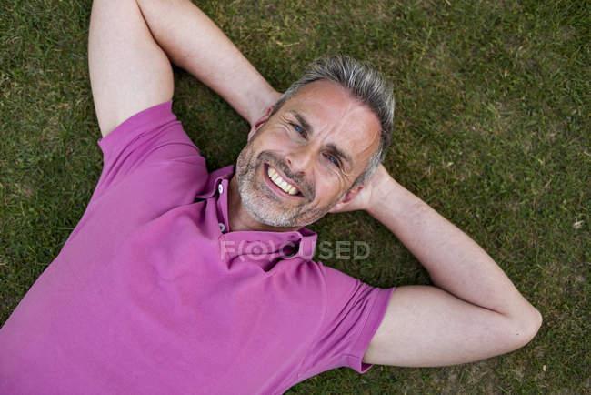 Retrato de homem maduro sorridente deitado na grama — Fotografia de Stock
