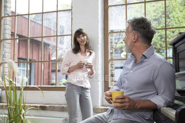 Pareja masculina en casa tomando un descanso, hablando y bebiendo café - foto de stock
