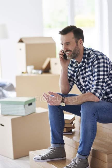 Uomo sorridente che si trasferisce nel nuovo appartamento parlando sul cellulare — Foto stock
