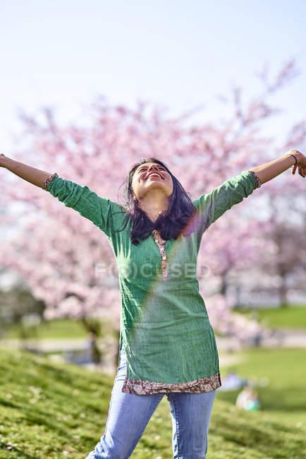 Щаслива молода жінка в парку на Вишневе дерево цвітіння — стокове фото