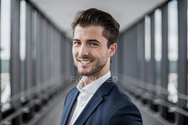 Ritratto di giovane uomo d'affari sorridente in un corridoio — Foto stock