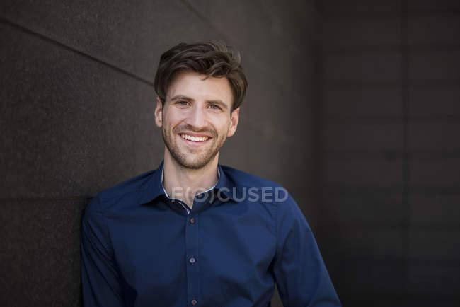 Portrait d'un homme d'affaires souriant appuyé contre un mur — Photo de stock