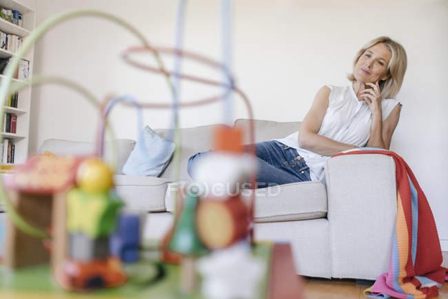 Mulher madura no sofá em casa olhando para brinquedos — Fotografia de Stock