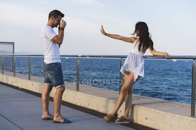 Young urban couple taking pictures at sea, woman making peace sign — Stock Photo