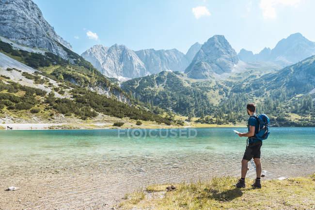 Austria, Tirol, Hombre de senderismo en el lago Seebensee, mirando el mapa - foto de stock