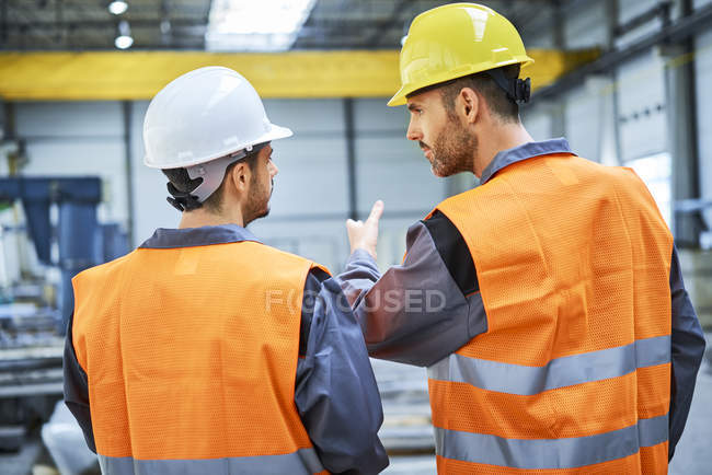 Rear view of men wearing protective workwear talking in factory — Stock Photo