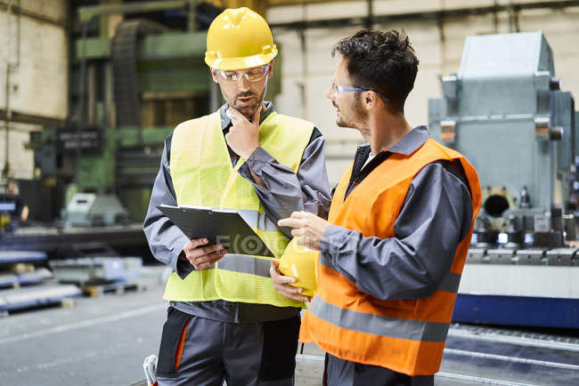 Men wearing protective workwear holding clipboard and talking in factory — Stock Photo