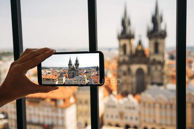 Chequia, Praga, mujer tomando fotos de la Iglesia de Nuestra Señora desde el antiguo ayuntamiento con teléfono inteligente, vista parcial - foto de stock