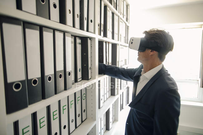 Businessman with VR goggles in company archive, searching shelf with files — Stock Photo