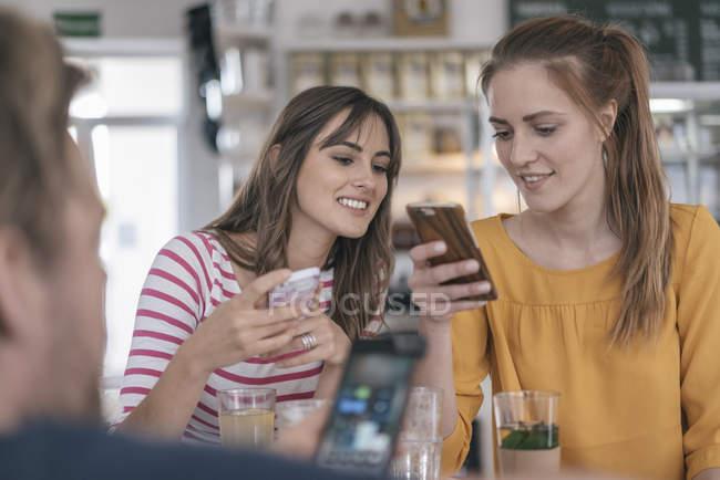Zwei Freundinnen treffen sich mit Smartphones in einem Café — Stockfoto