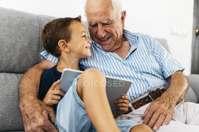 Niño feliz con tableta digital sentado con el abuelo en el sofá en casa y divirtiéndose - foto de stock