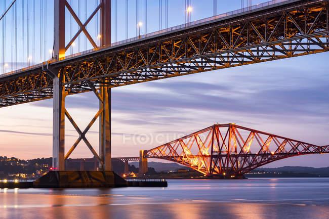 Reino Unido, Scotland, Fife, Edimburgo, Firth do estuário de Forth, ponte de Forth e ponte da estrada de Forth no por do sol — Fotografia de Stock