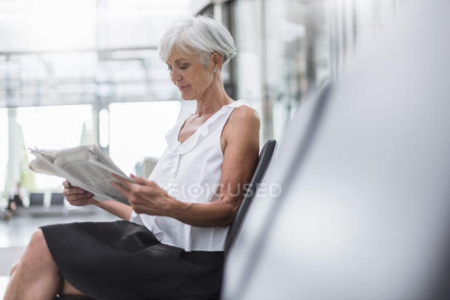 Senior woman sitting in waiting area and reading newspaper — Stock Photo