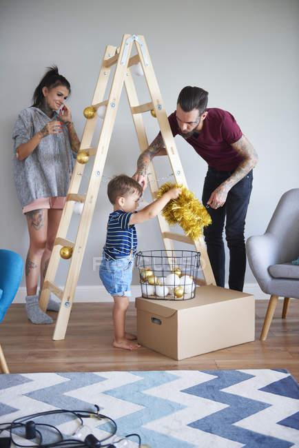 Современная семья украшает дом на Рождество, используя лестницу в качестве рождественской елки — стоковое фото