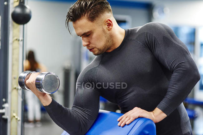 Man training with dumbbell in the gym — Stock Photo