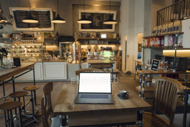 Ordenador portátil con pantalla en blanco en la cafetería - foto de stock