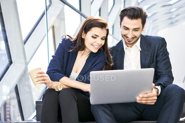 Smiling businesswoman and businessman sharing laptop on stairs in modern office — Stock Photo
