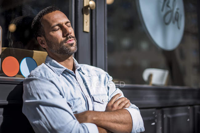 Розслаблена людина за межами кафе насолоджуючись сонцем — стокове фото