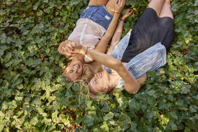 Two happy best friends lying on ground covered with ivy — Stock Photo