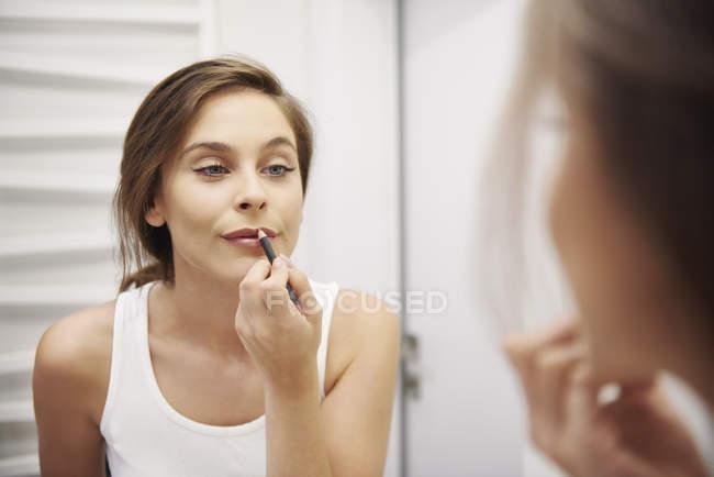 Mirror image of young woman in bathroom applying lipliner — Stock Photo