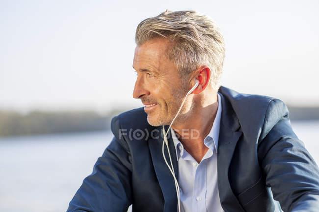 Empresário sorridente ouvindo música com fones de ouvido no lago — Fotografia de Stock