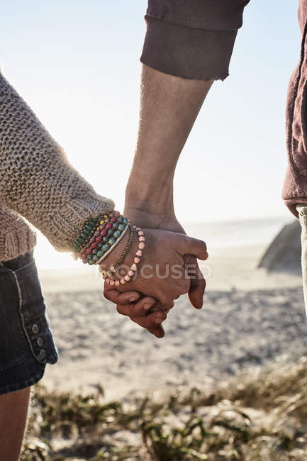 Close-up of couple holding hands at sunset on beach — Stock Photo