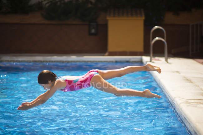 Bambina che salta testa prima in piscina in estate — Foto stock
