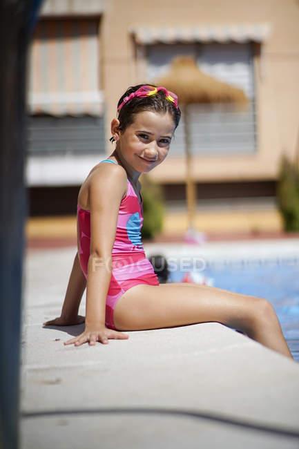 Bambina che indossa occhiali da nuoto seduta a bordo piscina — Foto stock