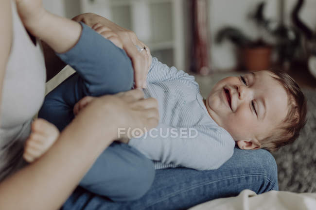 Мать обнимает маленького сына на коленях — стоковое фото