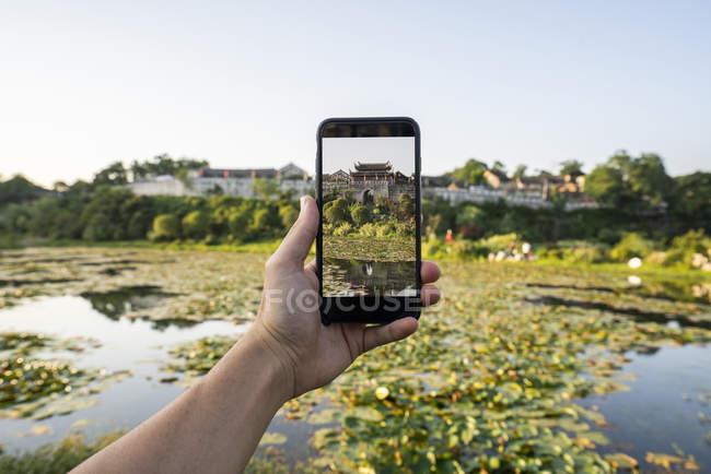 China, Qinyang, homem segurando smartphone e tirando foto de marco — Fotografia de Stock