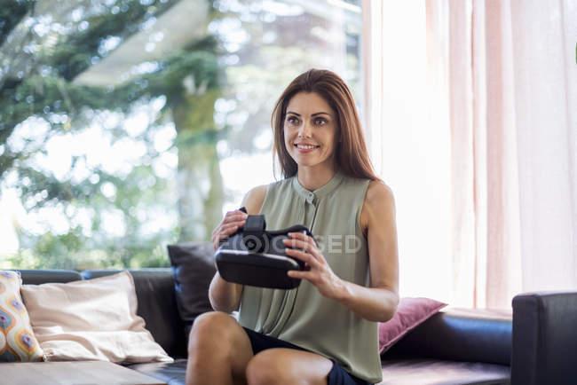 Улыбающаяся женщина сидит дома на диване, держа очки VR — стоковое фото