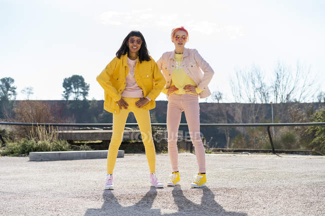 Two alternative friends wearing yellow and pink jeans clothes, posing — Stock Photo