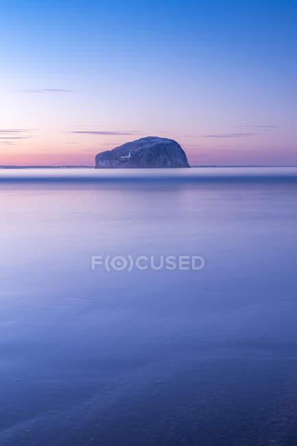 Royaume-Uni, Écosse, North Berwick, Firth of Forth, vue de Bass Rock avec phare au coucher du soleil, longue exposition — Photo de stock