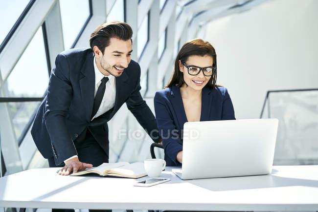 Посмішка бізнесмена і бізнесмена за столом у сучасному офісі. — стокове фото