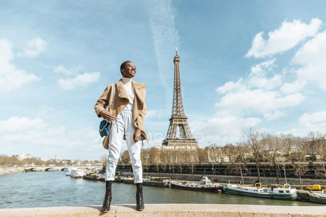 Francia, Parigi, Donna sorridente in piedi sul ponte con la torre Eiffel sullo sfondo — Foto stock
