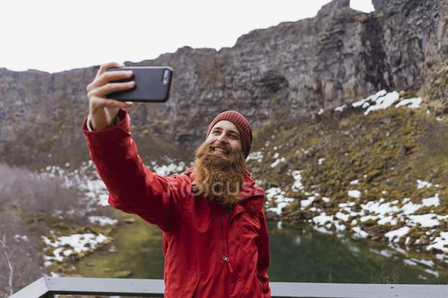 Исландия: улыбающийся бородатый мужчина с помощью смартфона делает селфи — стоковое фото