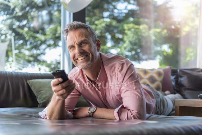 Sorridente uomo maturo sdraiato sul divano a casa con telecomando — Foto stock