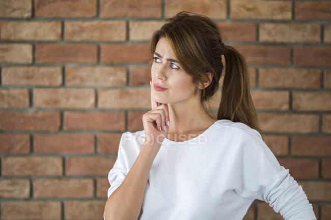 Портрет мыслящей девушки перед кирпичной стеной — стоковое фото
